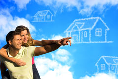 Happy couple under the blue sky dreaming of a hous. Happy couple under the blue sky enjoying the sun pointing to a house made of clouds Royalty Free Stock Photography
