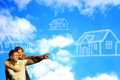 Happy couple under the blue sky dreaming of a hous. Happy couple under the blue sky enjoying the sun pointing to a house made of clouds Stock Image