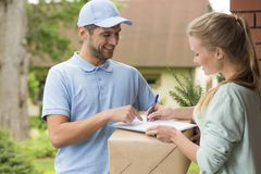 Courier in blue uniform and woman signing receipt of package delivery royalty free stock photos