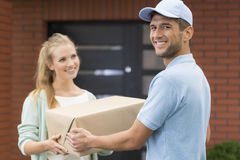 Happy courier delivering a package Stock Photography