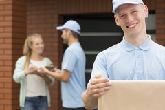 Happy courier holding a package for woman royalty free stock image
