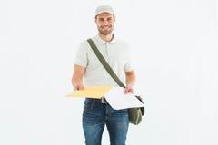 Happy courier man giving envelops. Portrait of happy courier man giving envelops on white background Stock Photos