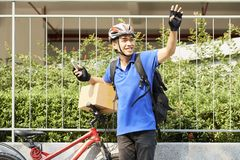 Happy courier waving with hand stock photos