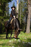Happy cowgirl on brown horse. Happy cowgirl in hat on brown horse Royalty Free Stock Photos