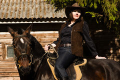 Happy cowgirl on brown horse Stock Images