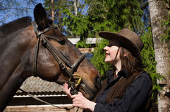 Happy cowgirl with brown horse Stock Photo