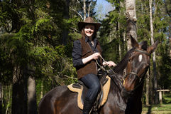 Happy cowgirl on brown horse Royalty Free Stock Images