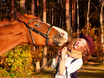 Happy cowgirl with her red horse. Royalty Free Stock Images