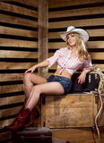 A happy cowgirl woman posing in a barn Stock Photography