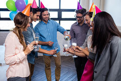 Happy coworker serving glasses of champagne for birthday Royalty Free Stock Photo