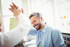 Happy coworkers giving high-five in creative office Stock Images