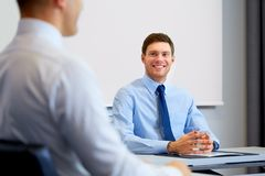 Happy coworkers meeting and talking at office. Business, people and teamwork concept - happy male coworkers meeting and talking at office Stock Image