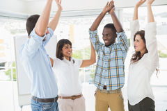 Happy coworkers standing and cheering together Royalty Free Stock Photo