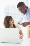 Happy coworkers using laptop together Royalty Free Stock Photos