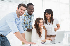 Happy coworkers working together with laptop Royalty Free Stock Photography