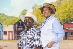 Happy Cowpoke Couple. A senior sitting cowboy by his standing wife in an old western town royalty free stock photography