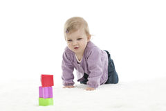 Happy crawling baby with colored cubes, isolated on white Royalty Free Stock Image