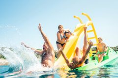 Happy crazy family hands up on floating Playground slide Catamaran as they enjoying sea trip as they have summer season vacation stock photo
