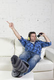 Happy crazy man on couch listening to music holding mobile phone as microphone Stock Image