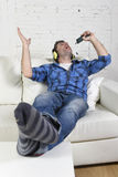 Happy crazy man on couch listening to music holding mobile phone as microphone Royalty Free Stock Photo