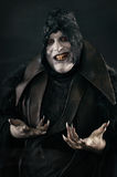 Happy crazy smiling vampire with large scary nails. Undead monst Stock Photography
