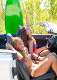 Happy crazy teen surfer girls smiling on car Stock Photos