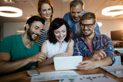 Happy creative business team discussing over digital tablet Stock Images