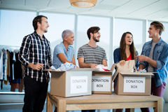 Happy creative business team sorting clothes in donation box Stock Photography