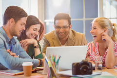 Happy creative business team using laptop in meeting Stock Photo