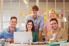 Happy creative business team using laptop in meeting Stock Image