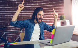 Happy creative businessman with arms raised looking at laptop. In office Stock Image