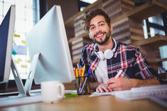 Happy creative businessman writing in book at computer desk Royalty Free Stock Image