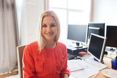 Happy creative female office worker with computers. Business, startup and people concept - happy businesswoman or creative female office worker with computers royalty free stock image