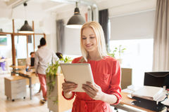Happy creative female office worker with tablet pc Stock Photography