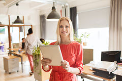 Happy creative female office worker with tablet pc Royalty Free Stock Photo