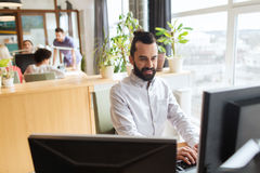Happy creative male office worker with computer Stock Images