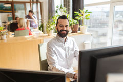 Happy creative male office worker with computer Stock Photo