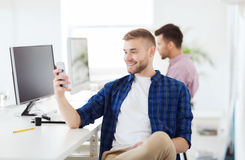 Happy creative man texting on cellphone at office. Business, technology, communication and people concept - happy young creative men or student with computer at Stock Photos