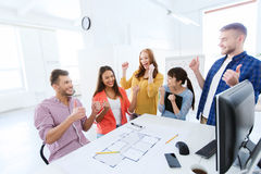Happy creative team celebrating success at office Stock Images