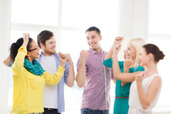 Happy creative team celebrating victory in office Stock Photos