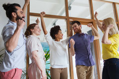 Happy creative team celebrating victory in office Stock Image