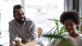 Happy creative team with coffee talking in office stock footage