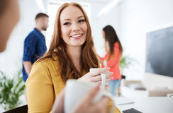 Happy creative team drinking coffee at office Stock Photos