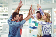 Happy creative team giving high fives to each other Stock Images