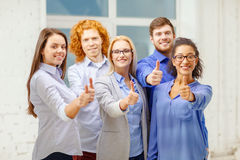 Happy creative team showing thumbs up in office Royalty Free Stock Images