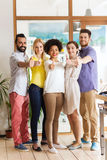 Happy creative team showing thumbs up in office Stock Photography