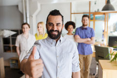 Happy creative team showing thumbs up in office Stock Image