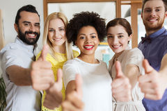 Happy creative team showing thumbs up in office Stock Images
