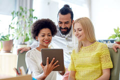 Happy creative team with tablet pc in office Royalty Free Stock Image