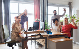 Happy creative team waving hands in office Royalty Free Stock Image